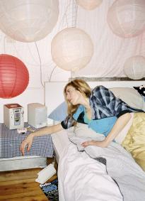 Eva - 28 - Pilotin: Schlafzimmer. Sie trägt Tops von Replay (grün), von Adidas Originals (türkis) und Jacke von Onitsuka Tiger.