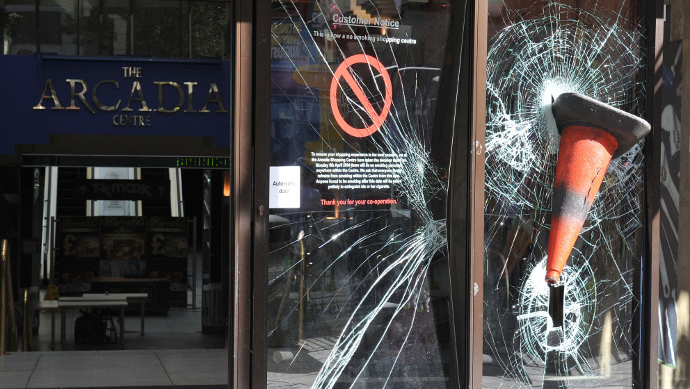 LONDON, ENGLAND - AUGUST 09:  A traffic cone is embedded in the smashed windows of the Arcadia shopping centre on Ealing Broa