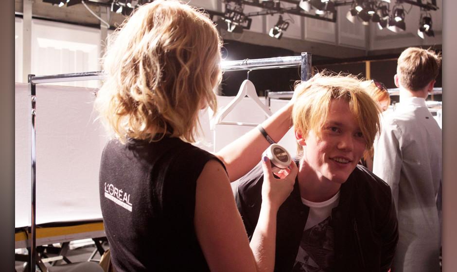 Ein Model bekommt den letzten Feinschliff vor der Show.