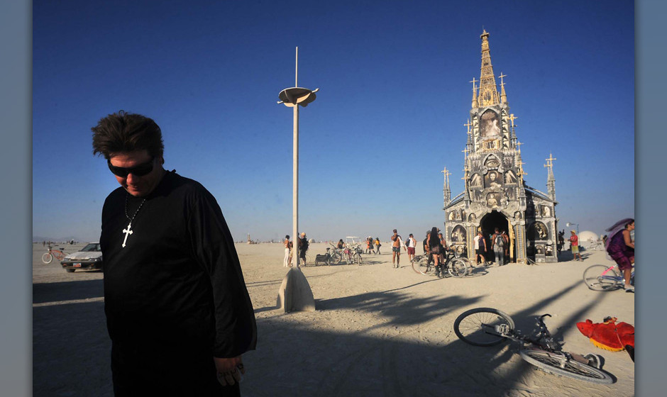 A man in a priest outfit walks away from the 'Photo Chapel' at the Burning Man festival in Gerlach, Nev. on Friday, Aug. 30,