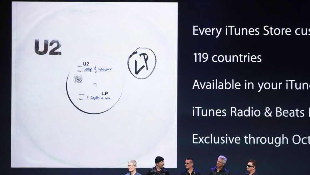 CUPERTINO, CA - SEPTEMBER 09:  Apple CEO Tim Cook (L) announces the free download of the new U2 album on iTunes as members of