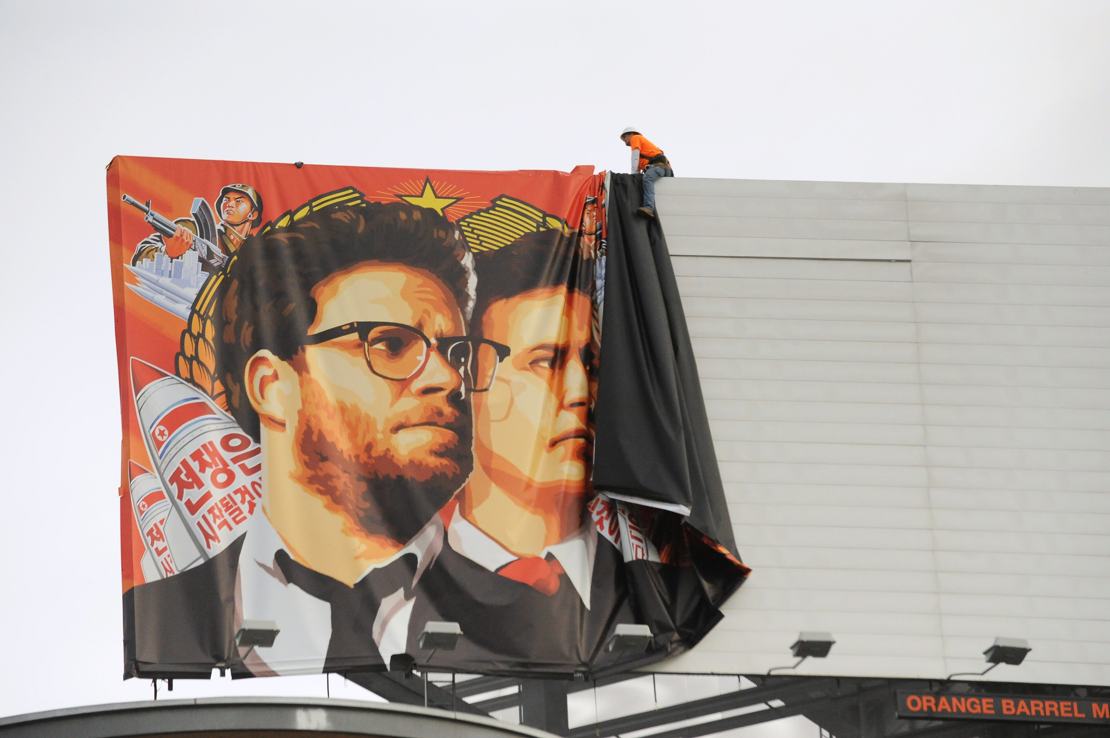 Workers remove a poster-banner for 'The Interview' from a billboard in Hollywood, California, December 18, 2014 a day after S