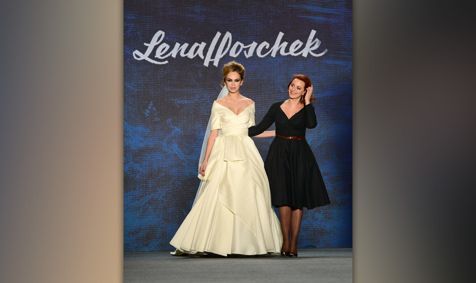 Austrian designer Lena Hoschek (R) walks with a model displaying her fashion at the Mercedes-Benz Fashion Week in Berlin on J
