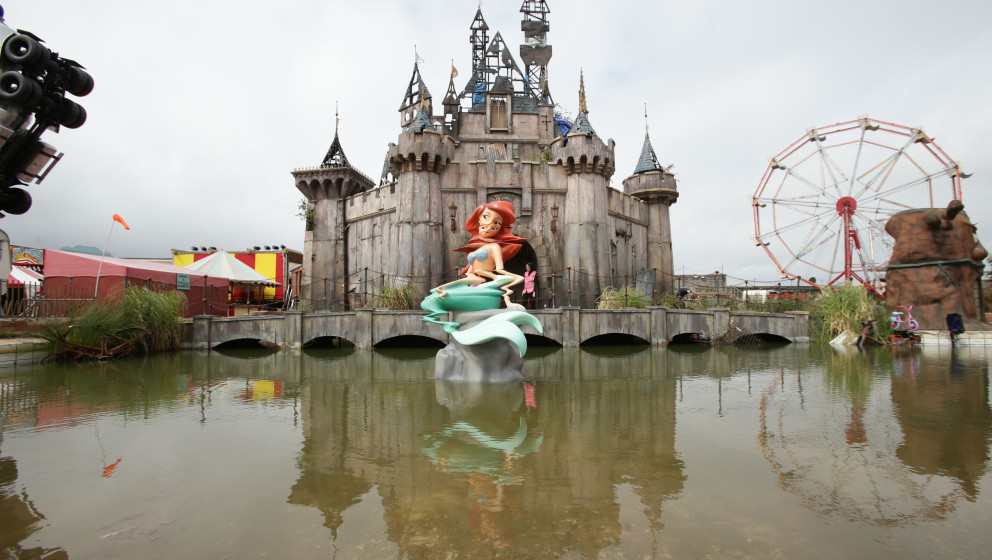 Banksy's Dismaland preview. A mermaid piece by Banksy, with a castle by Banksy and Block 9 in the background, during the pres