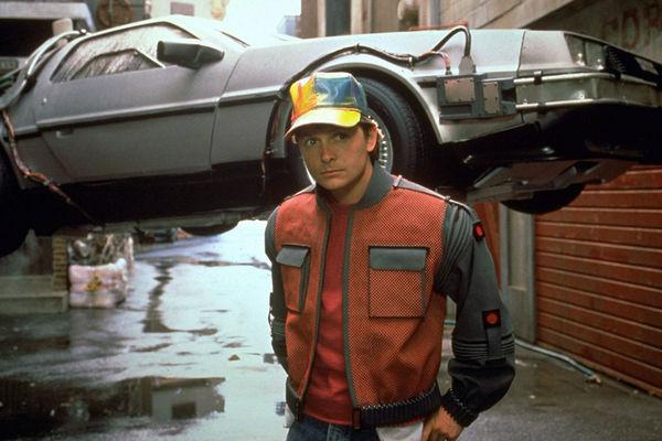 Michael J. Fox als Marty McFly vor dem legendären DeLorean