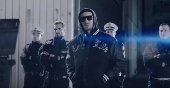 """Jan Böhmermann rappt zu """"Ich hab Polizei"""" in einer Bomberjacke mit der Aufschrift """"Cop Life"""""""