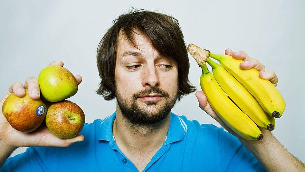 Man deciding whether to eat apple or banana (Photo by Universal Images Group via Getty Images)