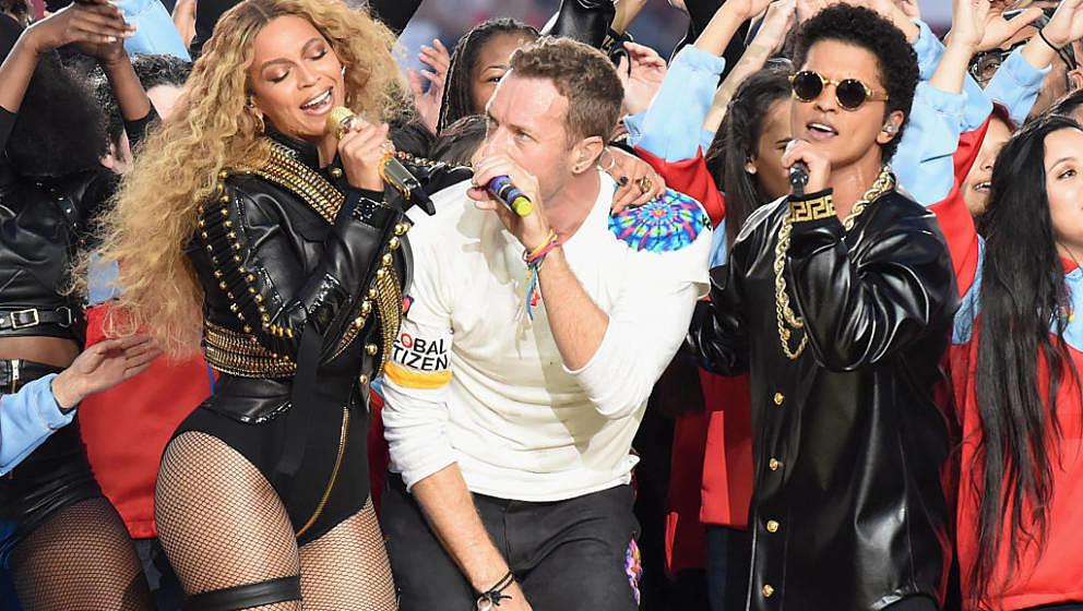 Chris Martin (M.) geht zwischen Beyoncé (l.) und Bruno Mars (r.) unter