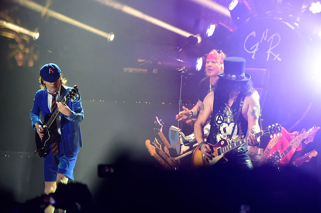 INDIO, CA - APRIL 16:  (L-R) Musician Angus Young of AC/DC performs onstage with Axl Rose and Slash of Guns N' Roses during d