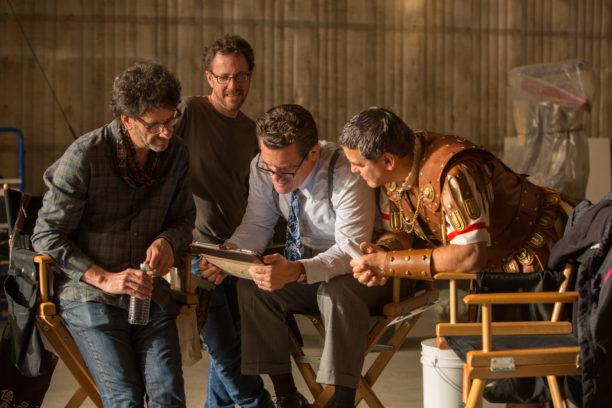 """Die Coen Brüder Ethan und Joel zusammen mit Josh Brolin und George Clooney am Set von """"Hail, Caesar!""""."""