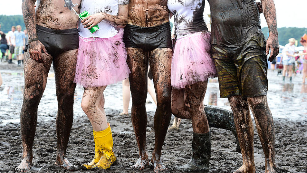 SCHEESSEL, GERMANY - JUNE 24: Visitors pose for a photo after taking a bath in a puddle at the camping site of the Hurricane