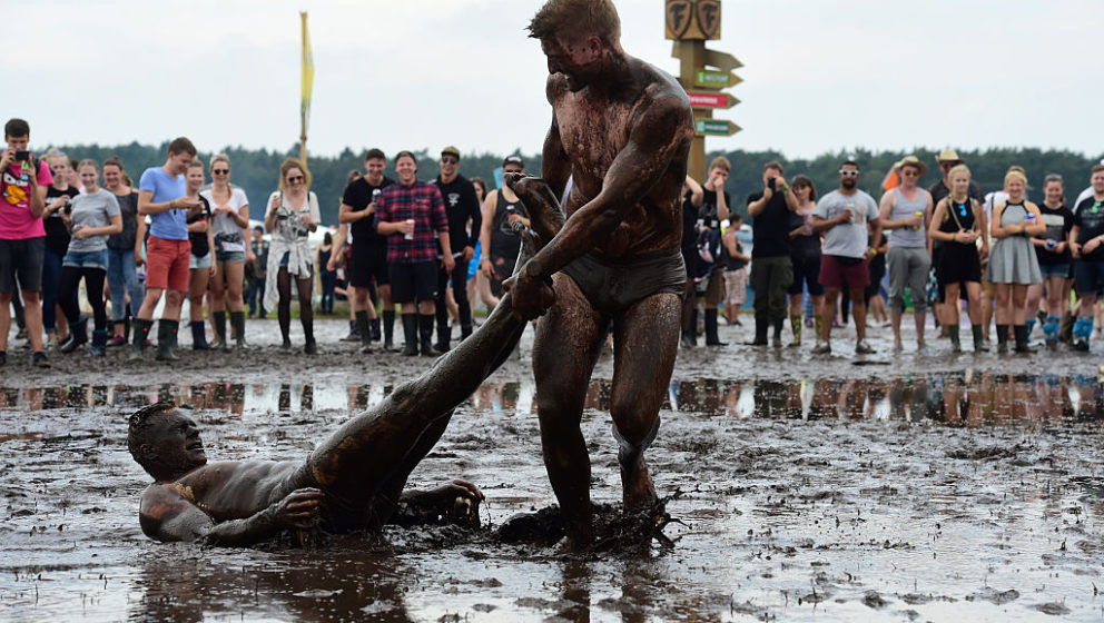 SCHEESSEL, GERMANY - JUNE 24: Male visitors take a bath in a mud puddle at the camping site of the Hurricane festival on June