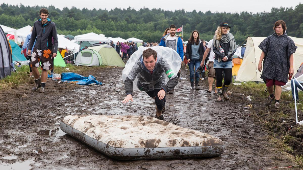 19/ Festival: Ein Festivalgast stuerzt sich auf eine im Schlamm liegende Luftmatratze auf dem Zeltplatz beim Hurricane Festiv