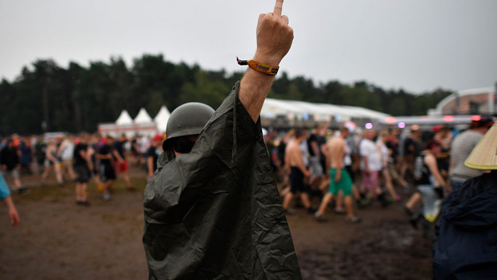 SCHEESSEL, GERMANY - JUNE 24: A visitor gestures during an evacuation of the Hurricane Festival compound following a thunders