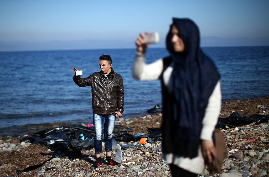 SIKAMINIAS, GREECE - NOVEMBER 14: Syrian refugees film their surroundings on their smart phones after making the crossing fro