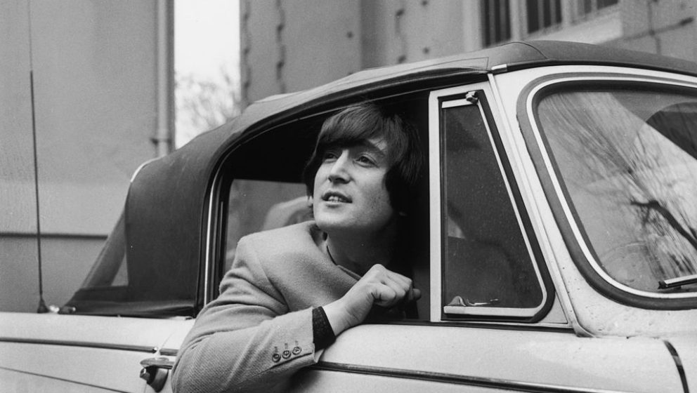 18th February 1965:  Singer, songwriter and guitarist John Lennon of The Beatles in his Triumph Herald convertible car.  (Pho