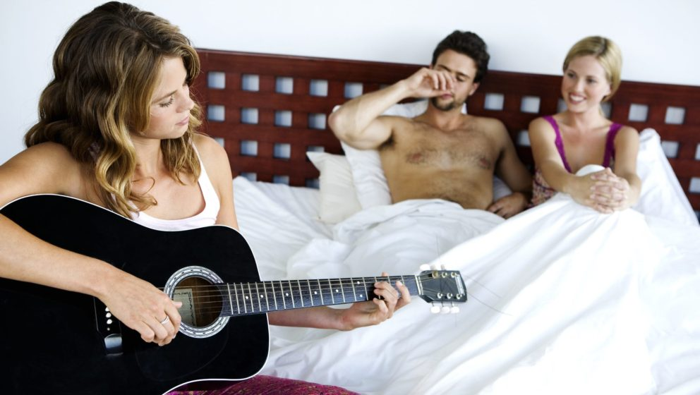 Young couple in bed listening to woman playing guitar