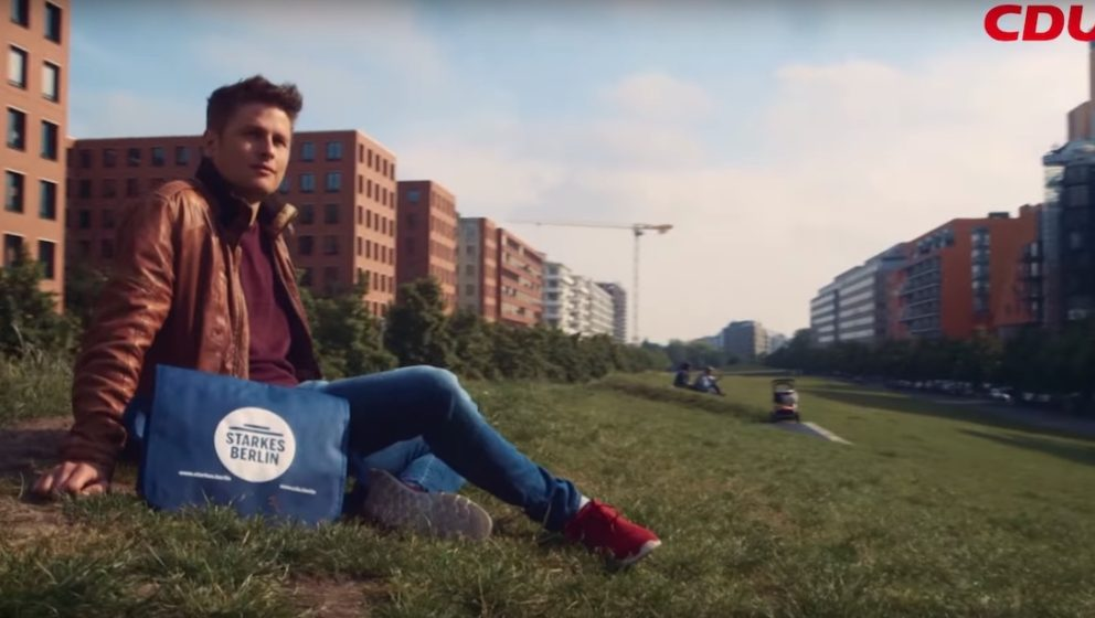 Junger Mann, der auf einer Wiese sitzt und für ein starkes Berlin ist.