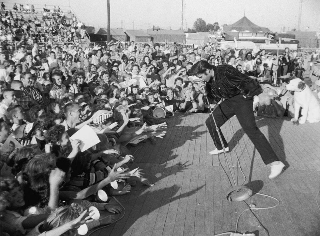 circa 1957: American singer and actor Elvis Presley (1935-1977) performing outdoors on a small stage to the adulation of a young crowd. (Photo by Hulton Archive/Getty Images)