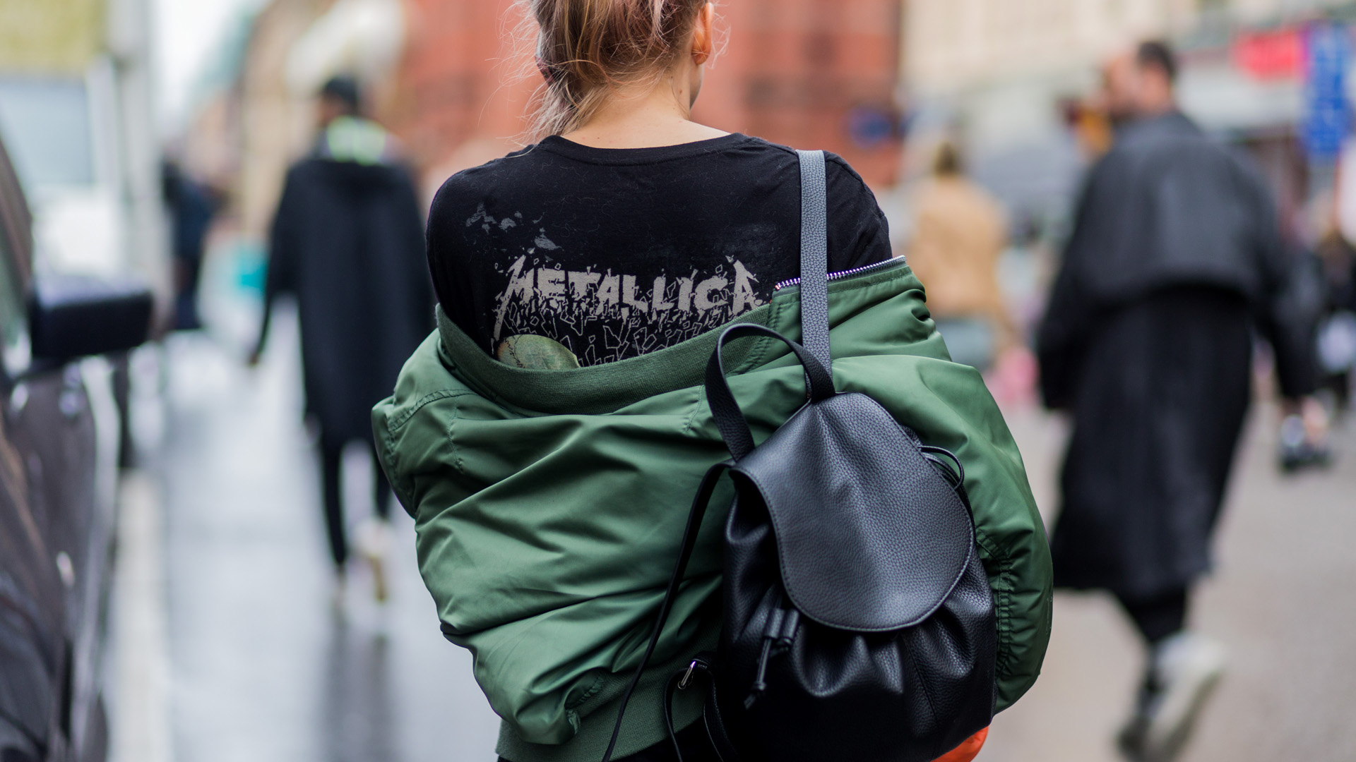 STOCKHOLM, SWEDEN - AUGUST 29: A guest wearing a black Metallica tshirt, olive bomber jacket and black backpack while having