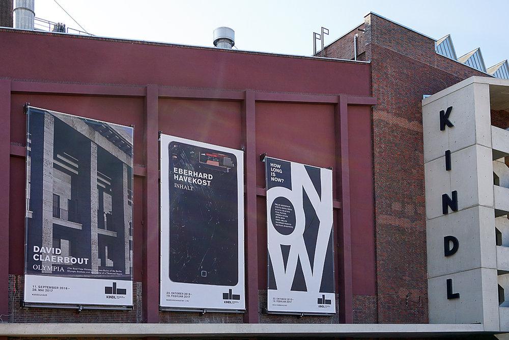 Die Ostfassade des KINDL - Zentrmu für zeitgenössische Kunst in rotem Backstein mit drei Plakaten der aktuellen Ausstellungen.