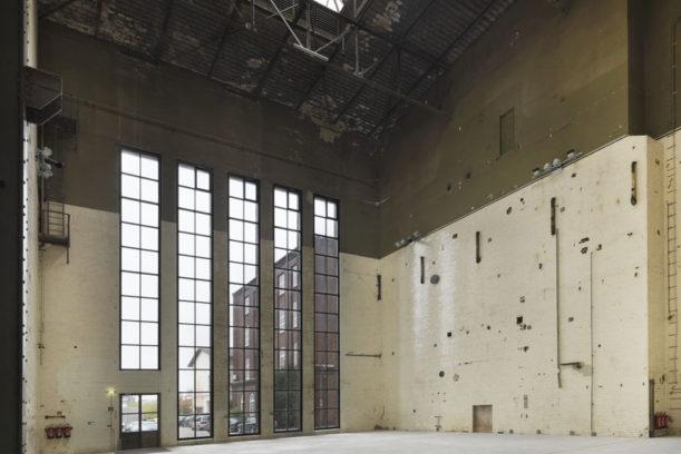 Der zwanzig Meter hohe Raum des Kesselhauses, der zur Hälfte weiß gefließt ist und deckenhohe Fenster besitzt.