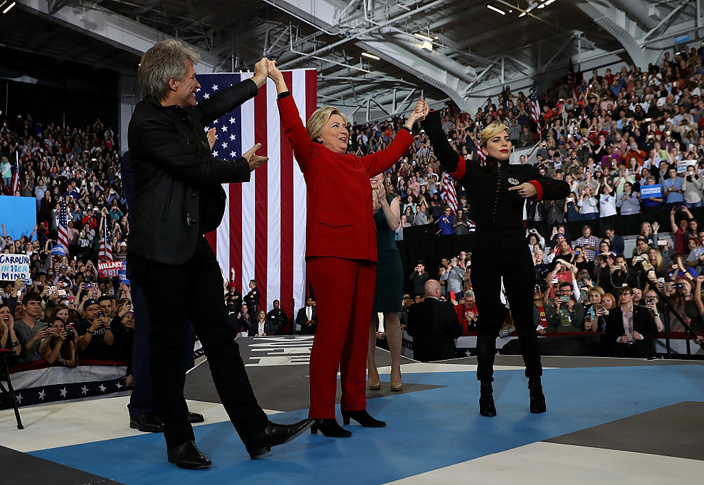RALEIGH, NC - NOVEMBER 08:  Democratic presidential nominee former Secretary of State Hillary Clinton (C) raises her arms wit