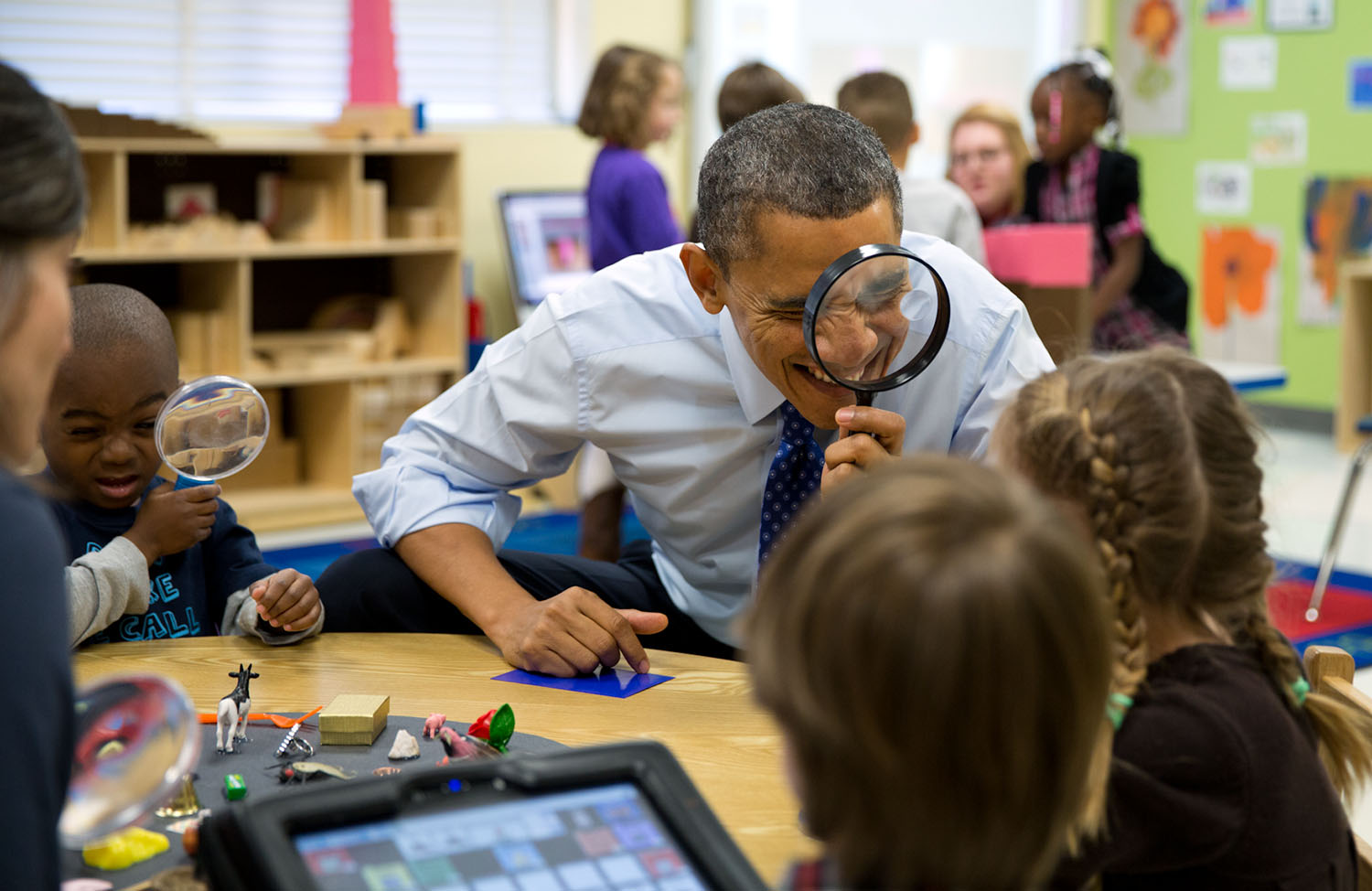 """Feb. 14, 2013 """"The President genuinely enjoys being with kids. Here, he played a magnifying glass game with children during a visit to a pre-kindergarten classroom at the College Heights Early Childhood Learning Center in Decatur, Georgia."""" (Official White House Photo by Pete Souza) This official White House photograph is being made available only for publication by news organizations and/or for personal use printing by the subject(s) of the photograph. The photograph may not be manipulated in any way and may not be used in commercial or political materials, advertisements, emails, products, promotions that in any way suggests approval or endorsement of the President, the First Family, or the White House."""