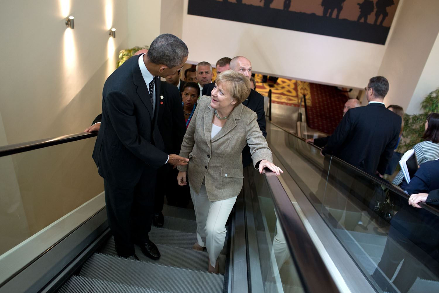 """Sept. 4, 2014 """"Meetings happen everywhere including on the escalator. Here, the President continues a conversation with German Chancellor Angela Merkel following their meeting with other leaders at the NATO Summit in Newport, Wales."""" (Official White House Photo by Pete Souza) This official White House photograph is being made available only for publication by news organizations and/or for personal use printing by the subject(s) of the photograph. The photograph may not be manipulated in any way and may not be used in commercial or political materials, advertisements, emails, products, promotions that in any way suggests approval or endorsement of the President, the First Family, or the White House."""