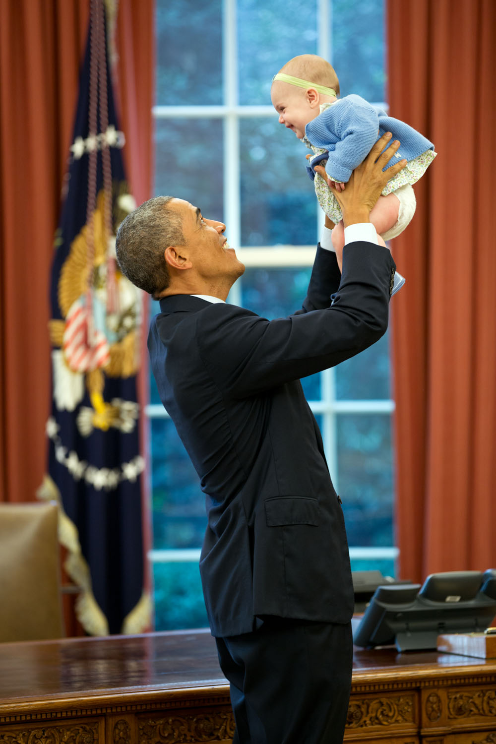 """Oct. 14, 2014 """"The President lifts the daughter of a departing staff member in the Oval Office."""" (Official White House Photo by Pete Souza) This official White House photograph is being made available only for publication by news organizations and/or for personal use printing by the subject(s) of the photograph. The photograph may not be manipulated in any way and may not be used in commercial or political materials, advertisements, emails, products, promotions that in any way suggests approval or endorsement of the President, the First Family, or the White House."""