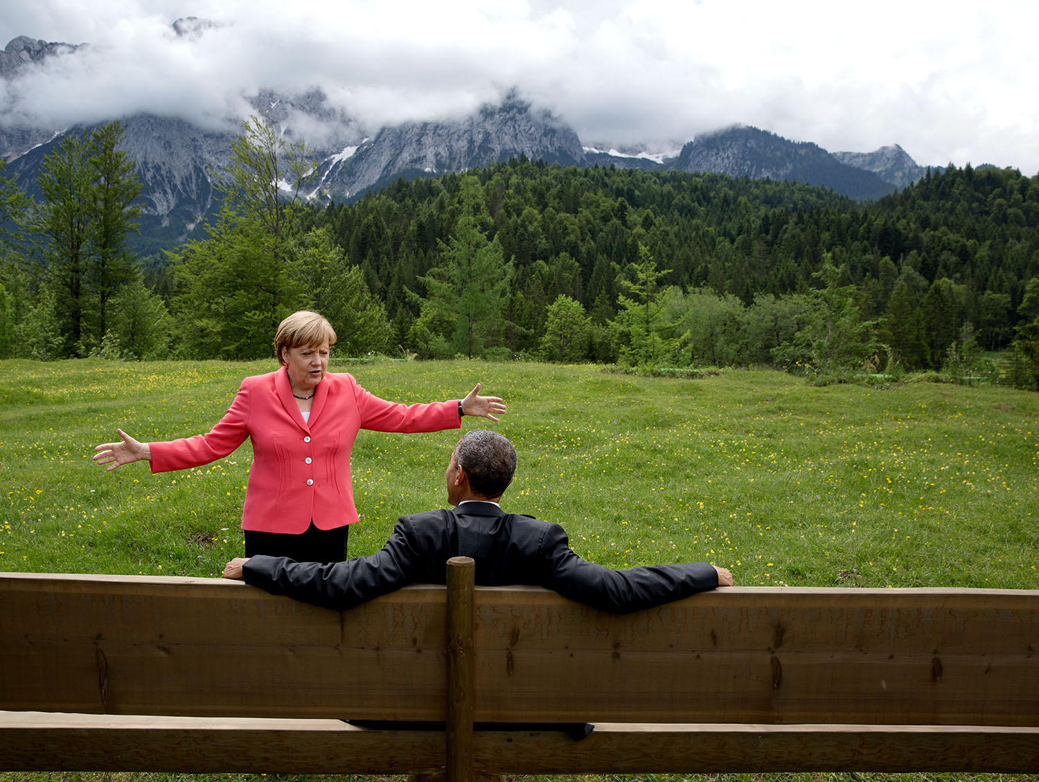 """June 8, 2015 """"We were at the G7 Summit in Krün, Germany. Chancellor Angela Merkel asked the leaders and outreach guests to make their way to a bench for a group photograph. The President happened to sit down first, followed closely by the Chancellor. I only had time to make a couple of frames before the background was cluttered with other people."""" (Official White House Photo by Pete Souza) This official White House photograph is being made available only for publication by news organizations and/or for personal use printing by the subject(s) of the photograph. The photograph may not be manipulated in any way and may not be used in commercial or political materials, advertisements, emails, products, promotions that in any way suggests approval or endorsement of the President, the First Family, or the White House."""