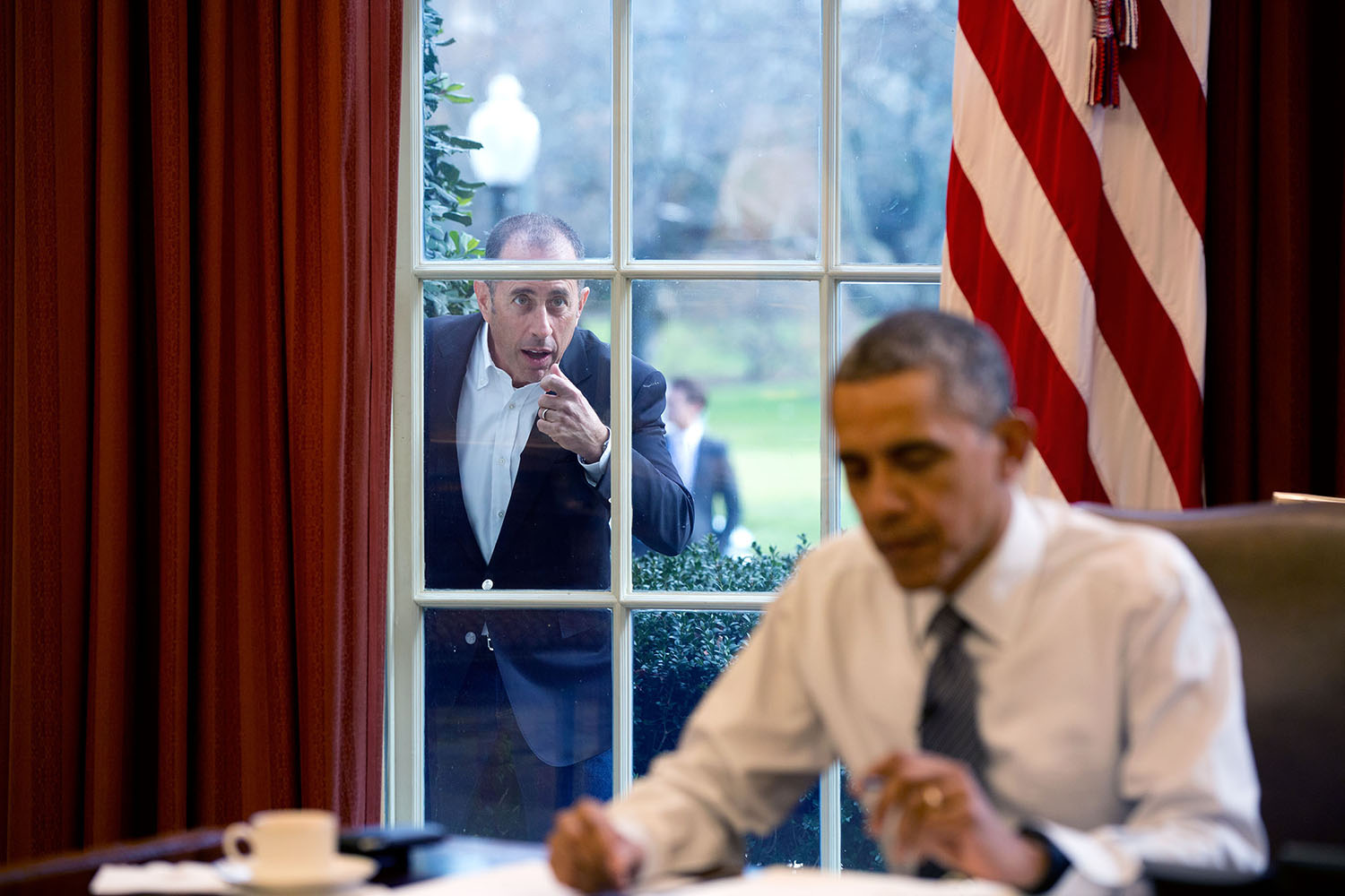 """Dec. 7, 2015 """"Comedian Jerry Seinfeld knocks on the Oval Office window to begin a segment for his series, 'Comedians in Cars Getting Coffee.'"""" (Official White House Photo by Pete Souza) This official White House photograph is being made available only for publication by news organizations and/or for personal use printing by the subject(s) of the photograph. The photograph may not be manipulated in any way and may not be used in commercial or political materials, advertisements, emails, products, promotions that in any way suggests approval or endorsement of the President, the First Family, or the White House."""