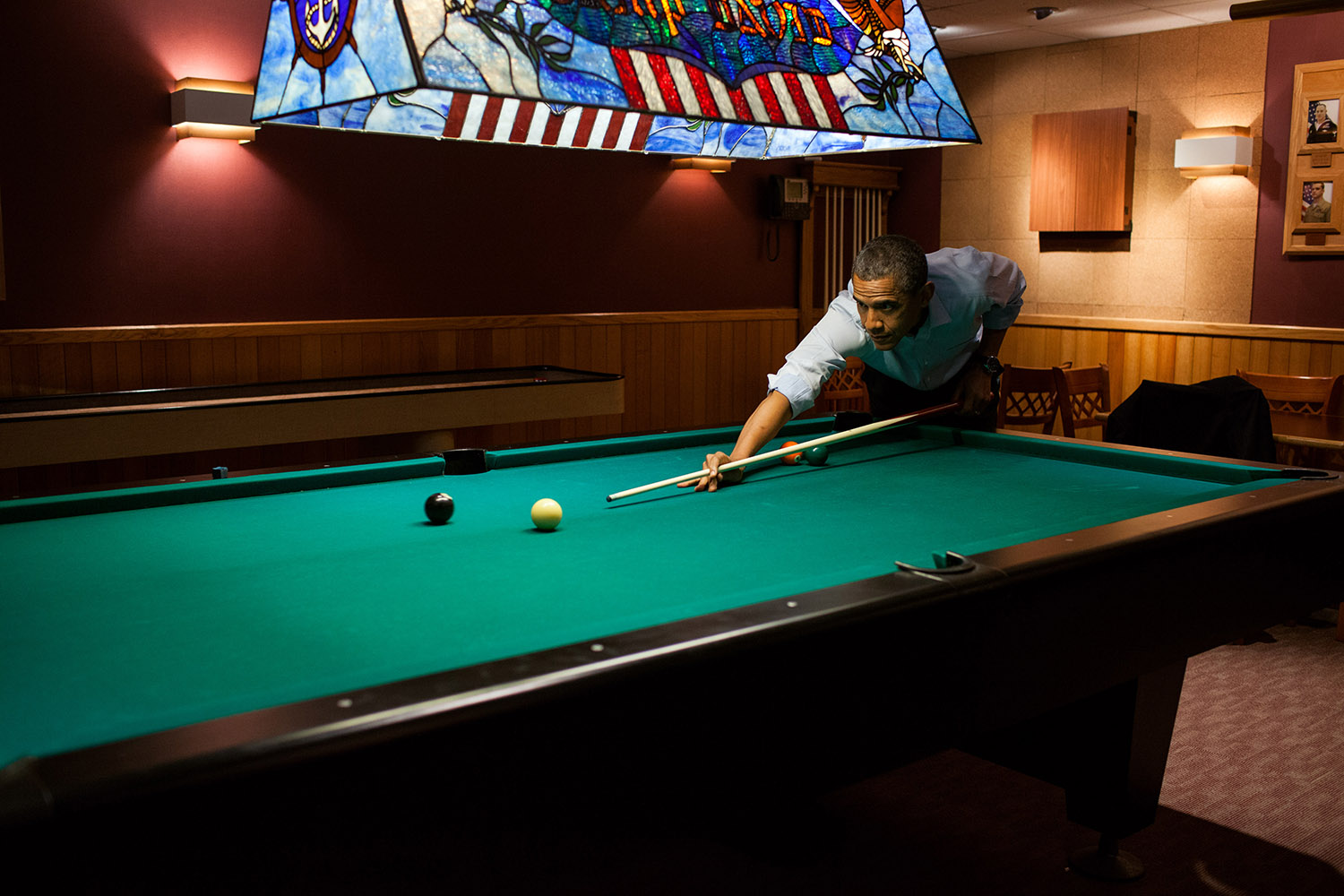 """May 19, 2012 """"Following the conclusion of the G8 Summit, the President plays a game of pool in the Holly Cabin at Camp David."""" (Official White House Photo by Pete Souza) This official White House photograph is being made available only for publication by news organizations and/or for personal use printing by the subject(s) of the photograph. The photograph may not be manipulated in any way and may not be used in commercial or political materials, advertisements, emails, products, promotions that in any way suggests approval or endorsement of the President, the First Family, or the White House."""