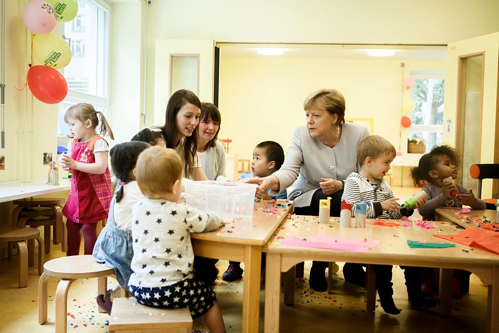 BERLIN, GERMANY - JUNE 21: German Chancellor Angela Merkel chats with children during her visit to the Weydemeyerstrasse Kind