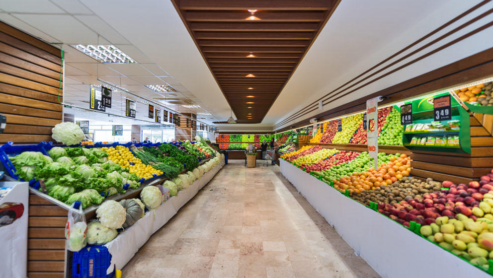Produce Section in a Supermarket - A supermarket, a large form of the traditional grocery store, is a self-service shop offering a wide variety of food and household products, organized into aisles. It is larger in size and has a wider selection than a traditional grocery store, but is smaller and more limited in the range of merchandise than a hypermarket or big-box shop. The supermarket typically comprises meat, fresh produce, dairy, and baked goods aisles, along with shelf space reserved for canned and packaged goods as well as for various non-food items such as household cleaners, pharmacy products and pet supplies. Most supermarkets also sell a variety of other household products that are consumed regularly, such as alcohol (where permitted), medicine, and clothes, and some stores sell a much wider range of non-food products.