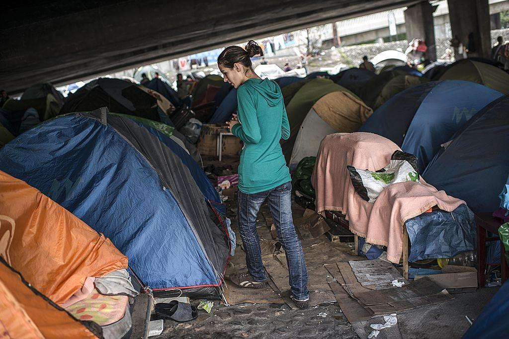 LYON, FRANCE - OCTOBER 23: A woman walks near her tent in an illegal campsite of Albanian asylum seekers, situated under the A6 motorway's Kitchener bridge next to the entrance of the Fourviere tunnel on October 23, 2013 in Lyon, France. A court today ordered the immediate expulsion of the camp of 300 people, including 98 children, who have been camping beneath the highway bridge since July. The interior ministry also said today that it would seek an overhaul of the asylum system. (Photo by Alexander Roth-Grisard/Getty Images)