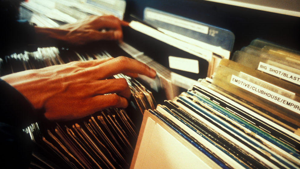 A man's fingers running along the sleeves of vinyl in a record shop, London, UK 1998