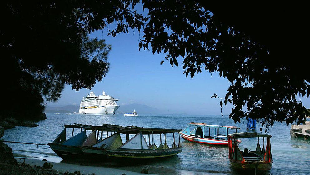 Schiff in der Karibik mit Booten davor und ein bisschen Meer, Bäume sind auch dabei.
