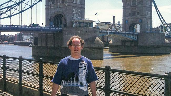 Sam Barksy vor der Tower Bridge, mit einem Pulli mit Tower Bridge vorne drauf.
