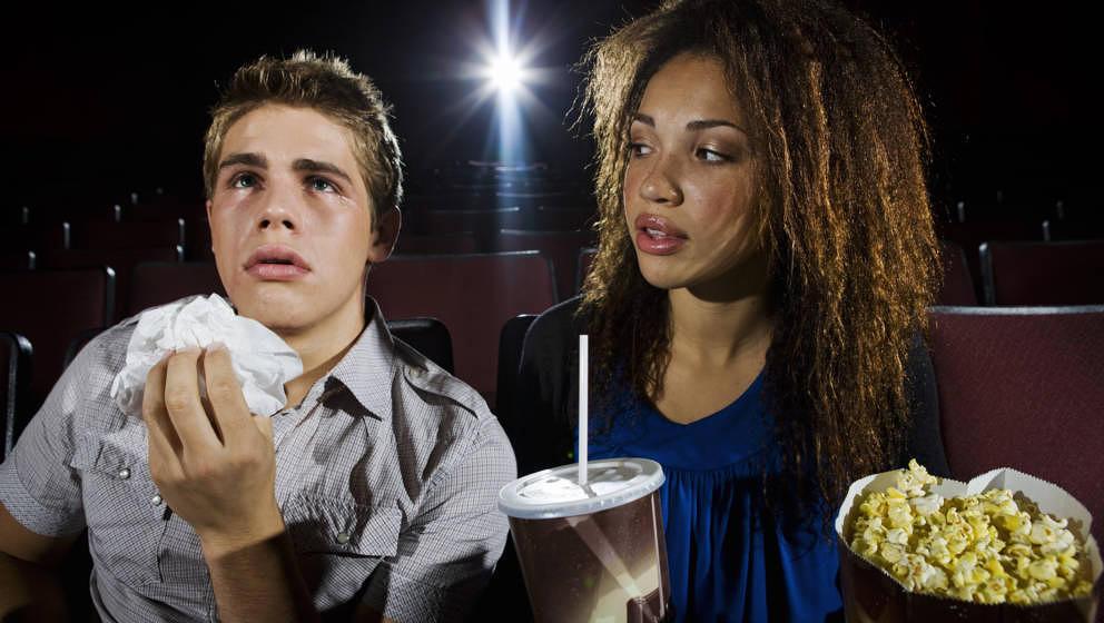 Junger Mann und junge Frau im Kino, er weint