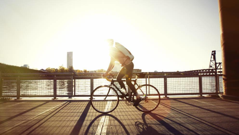 A woman bike commuting along the Portland Oregon waterfront trail.