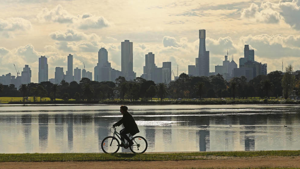 MELBOURNE, AUSTRALIA - JUNE 16:  A person cycles along Albert Park Lake on an Autumn day with  high-rise and apartment buildi