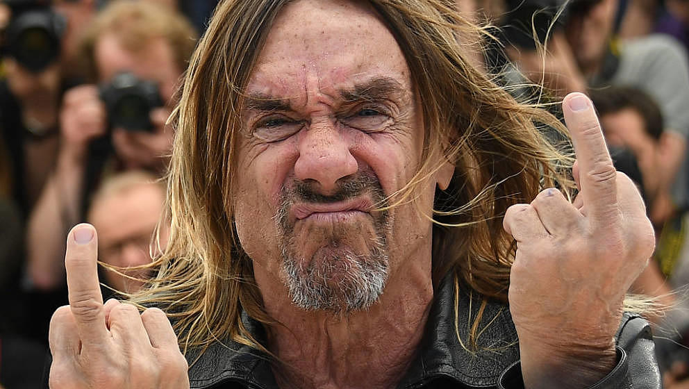 US singer Iggy Pop gives the fingers while posing on May 19, 2016 during a photocall for the film 'Gimme Danger' at the 69th