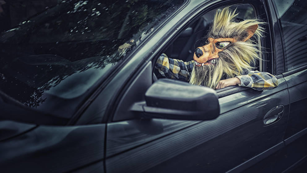 Mixed race boy wearing wolf mask and driving car