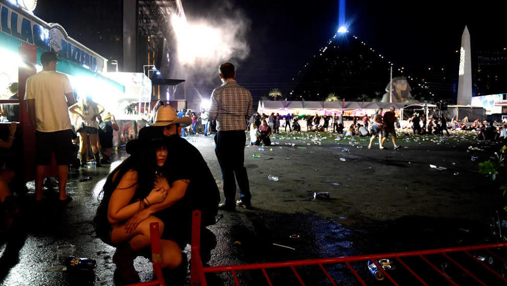 LAS VEGAS, NV - OCTOBER 01:  People take cover at the Route 91 Harvest country music festival after apparent gun fire was hea