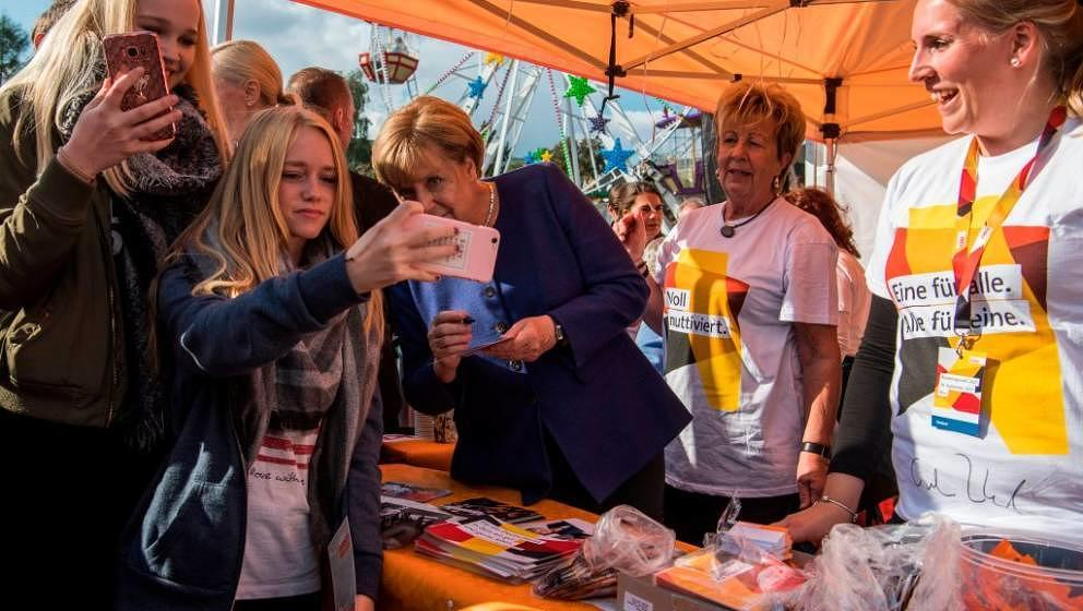 Teenagers take a selfie with German Chancellor Angela Merkel (C) as she signs autographs at a neighbourhood fair organised by
