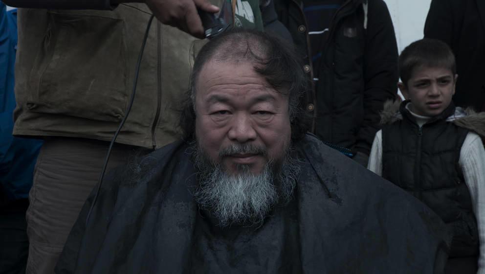 Ai Weiwei lässt sich von einem Flüchtling die Haare rasieren.