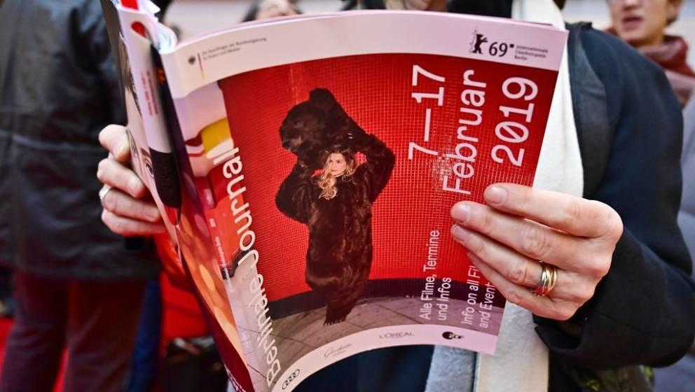 A woman holds a Berlinale programme as she waits for the presale of tickets for the Berlinale film festival in a shoppping ma