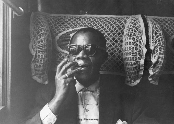 Jazz trumpeter and singer Louis Armstrong (1901-1971) pictured moisturizing his lips while travelling on a train during his t