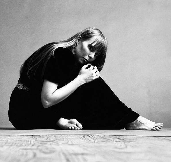 Portrait of Canadian musician Joni Mitchell wearing a black short-sleeved dress with several necklaces, November 1968. This i